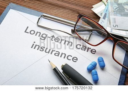 Text LONG-TERM CARE INSURANCE on information clipboard, closeup. Medical concept
