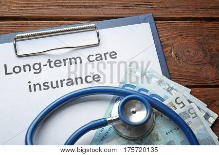Text LONG-TERM CARE INSURANCE on clipboard with stethoscope and money on wooden table closeup