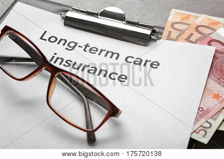 Text LONG-TERM CARE INSURANCE on clipboard with glasses and euros closeup