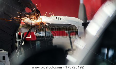 Professional car service - worker grinding metal construction with a circular saw, telephoto