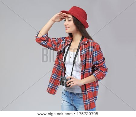 Beautiful female tourist with camera looking around, on grey background
