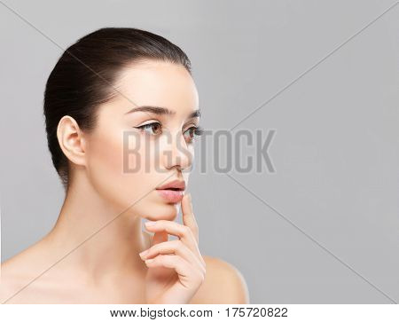 Woman with cold sore touching lips on light background