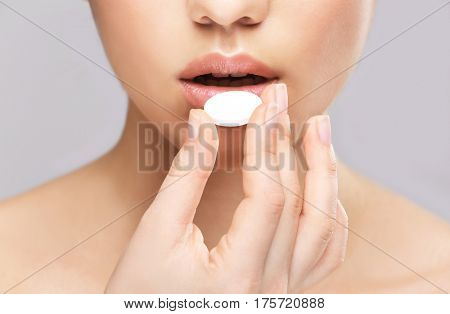 Beautiful woman taking pill on light background
