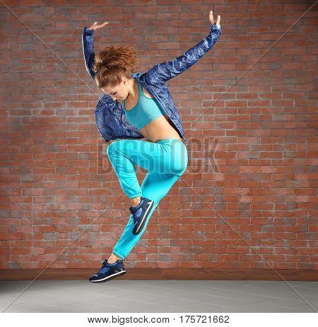 Beautiful young hip-hop dancer jumping against brick wall