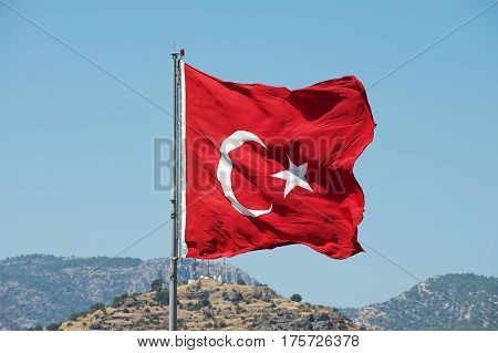 Turkish National flag at the flagpole waves over a hill with a blue summer sky at the background in Bodrum, Turkey.
