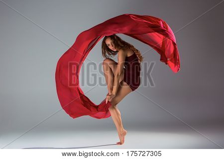 Young beautiful woman dancer in red swimsuit posing on a light grey studio background. Contemporary
