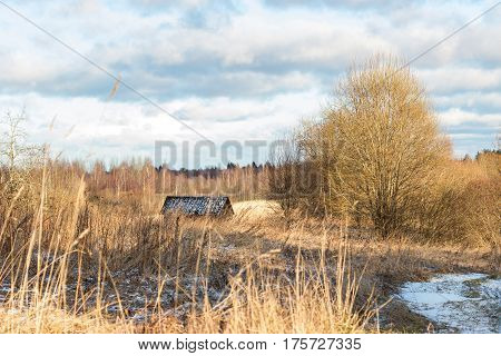 Beautiful winter landscape with a field, a house, a forest and a little snow on a sunny day.
