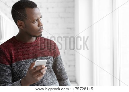 Handsome And Pensive Young African American Student In Cozy Sweater, Looking Though Window, Holding