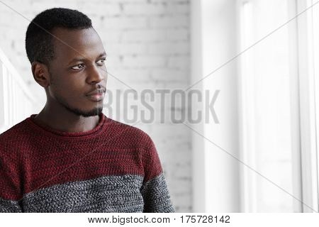 Close Up Portrait Of Attractive Young Dark-skinned Designer Having Rest, Standing At White Window Fr