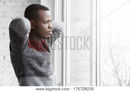 Half Profile Of Handsome Tired Young Dark-skinned Graphic Designer In Grey Sweater Keeping Hands Up