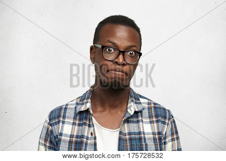Funny Emotional Bug-eyed Dark-skinned Male Student Wearing Spectacles Holding Breath With Pursed Lip