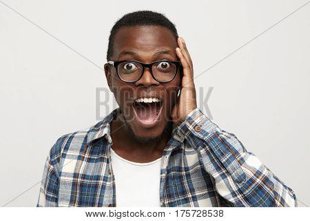 Amazed Young African American Hipster Wearing Glasses And Checkered Shirt Over White T-shirt Touchin