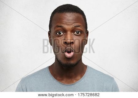 Close Up Shot Of Funny Young African American Man Dressed Casually Pouting Lips And Raising Brows, E