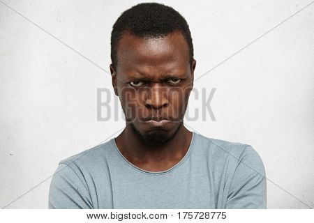 Studio Portrait Of Displeased, Angry, Grumpy And Pissed Off Young African American Male Looking And