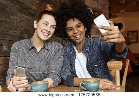 Cute Lesbian Couple Having Fun Indoors: Fashionable African American Woman With Afro Haircut Holding