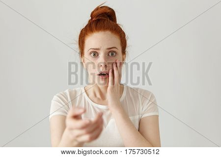 Human Facial Expressions, Emotions And Feelings. Beautiful Redhead Girl With Hair Knot Having Scared