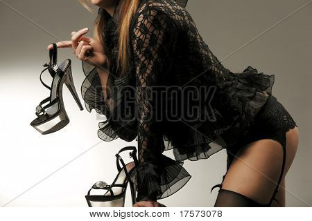 Striptease performer wearing black nightgown and lingerie holding shoes with high heel