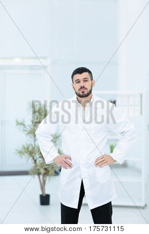 Smiling doctor posing with arms crossed in the office, he is wearing a medical staff on the background