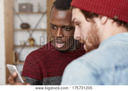 Dark-skinned Man And His Caucasian Bearded Hipster Surfing Internet On Cell Phone, Staring At Screen