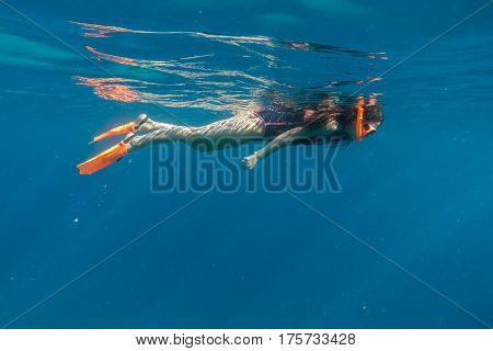 Girl in swimming mask and flippers dive in Red sea, underwater shoot