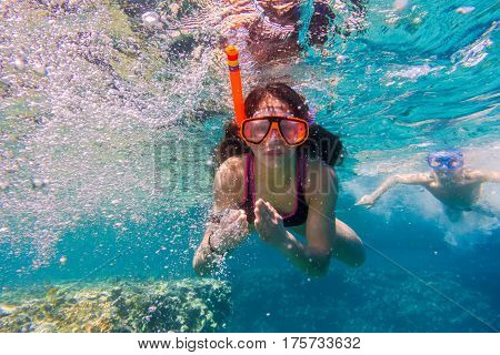 Girl and boy in swimming mask dive in Red sea near coral reef, underwater shoot