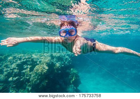 Boy in swimming mask dive in Red sea near coral reef, underwater shoot