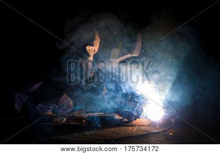 Welder brews metal constructions in dark room