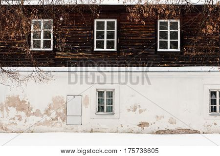 Old building in winter season. Plaster and wood wall with some windows. Architecture background