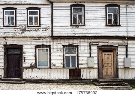 Old white wooden plank wall with some windows and doors. Architecture background