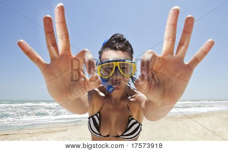 Happy diving girl in a swimming mask and snorkel showing okay sign. Funny picture.