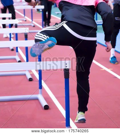An athlete warming up for the hurdles at a track and field competition