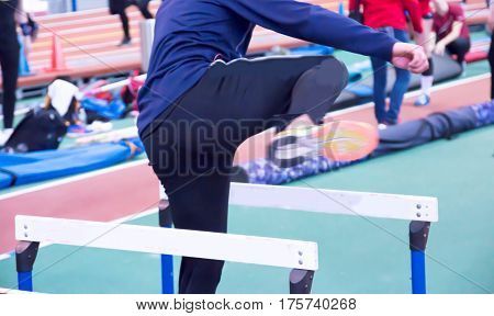 An athlete warms up for their race doing hurdle drills on the infield of an indoor track and field arena