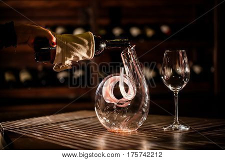Wine pouring from a bottle into carafe. Wine vault location.