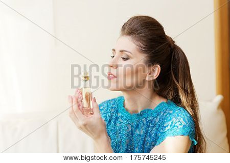 Portrait Of A Young Woman Holding A Bottle Of Perfume Her Hands