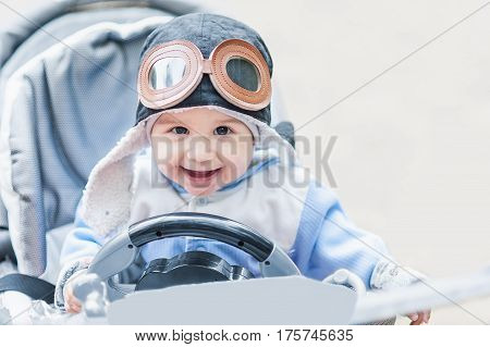 Cute Smiling Baby In The Cap Of The Pilot