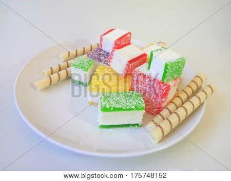 Multicolored marmalade sliced in pieces on a white plate - harm of sweet