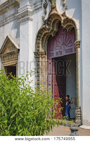 Old Goa, India - November 13, 2012: Unidentified tourist visit to the famous landmark - Convent and Church of St. Francis of Assisi - Roman Catholic church. A boy stands at the entrance to the Church