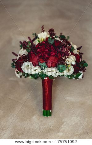 luxurious wedding bouquet with red ribbon made of roses and peony in a stone niche in a wall