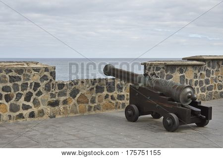 Old canon standing on a old fortress pointing out to the sea picture from Puerto de la Cruz Tenerife Spain.