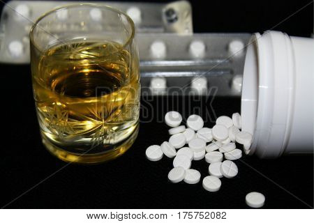 Benzodiazepines or other pills and glass of alcohol illustrative photo dangerous of overdose suicide depression drug addiction... not taken drugs and alcohol together.