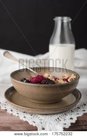 Milky soup with granola in brown bowl.