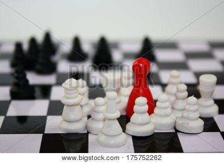 Fear from refugees concept. Migration in usa or europe theme. Chess pieces and bright red leader figure on chessboard.