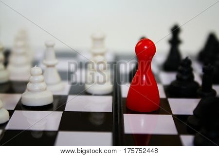 Chess game with bright red figurine for ludo on chessboard with other chess pieces.