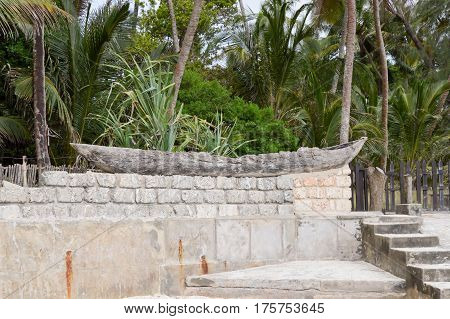 Old wooden canoe posing on a low wall separating Bamburi beach in Kenya from holiday makers