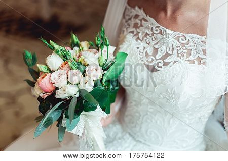 bride in a luxurious wedding dress with lace holding wedding bouquet made of biege and white roses.