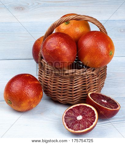 Ripe Blood Oranges Full Body and Two Halves in Wicker Basket closeup on Blue Wooden background
