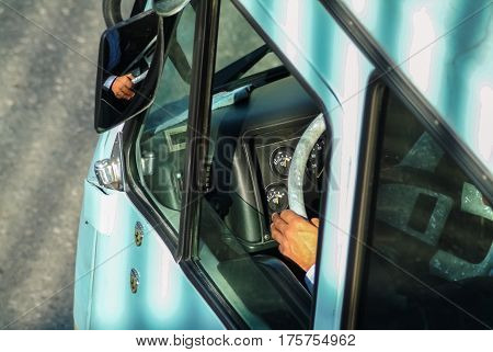 High angle view of a minibus driver hand on the steering wheel