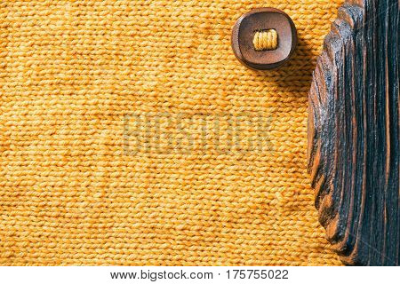 Combination of yellow wool and brown wood textures with wood button. Close-up direct view