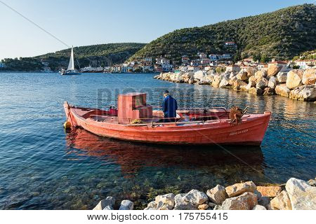 THESSALY, GREECE - OCTOBER 14, 2016: An old fisherman works in his traditional wooden boat in October 14, 2016 in Agia Kiriaki village in Greece. Fishing in wooden traditional boats remains an important part of the local economy in Greece.