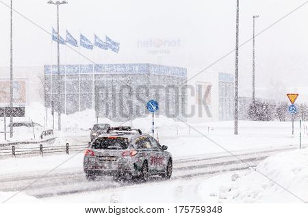 UMEA, SWEDEN ON MARCH 02. View of a modern highway, the traffic in snowy condition on March 02, 2017 in Umea, Sweden. Buildings in the background. Editorial use.